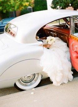 Auto ancienne, porte ouverte sur une mariée